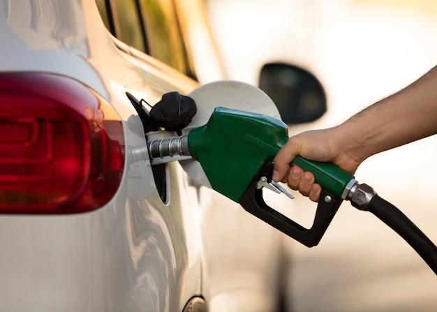 Witte auto bij tankstation wordt gevuld met brandstof