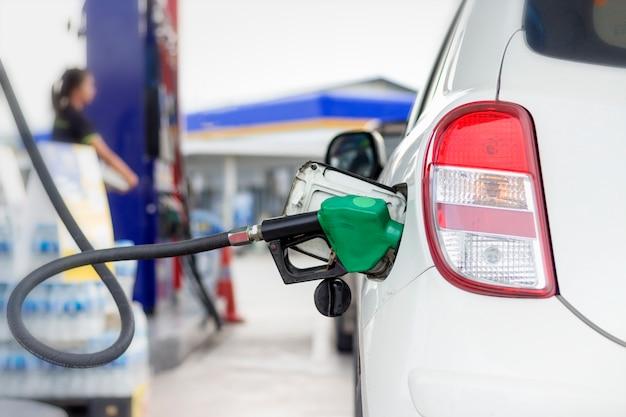 Witte auto bijtankende benzine door autodistributiemondstuk bij benzinepost met warm zonlicht