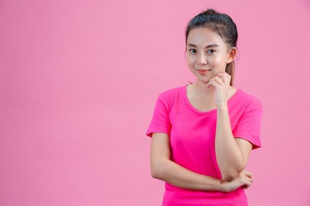 Witte aziatische vrouwen dragen roze shirts. steek zijn linkerhand in zijn gezicht op het roze.