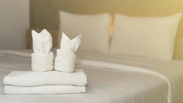 Witte badhanddoek op het interieur van de beddecoratie in het hotel.