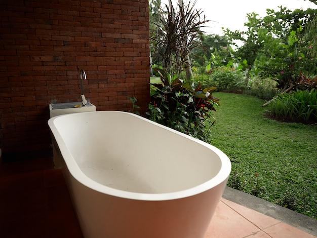 Witte badkamer bij bakstenen muur en landschap op de achtergrond eenheid met de natuur with
