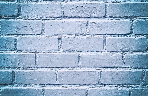 Witte bakstenen muur met een blauwe tint.