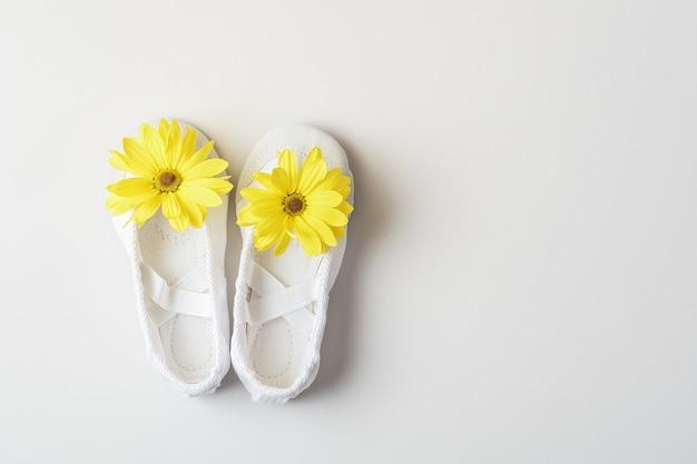 Witte ballerina's met gele bloemen op een met kopie ruimte.