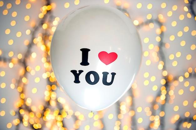 Witte ballon met ik hou van je geschreven met sprankelende bokeh