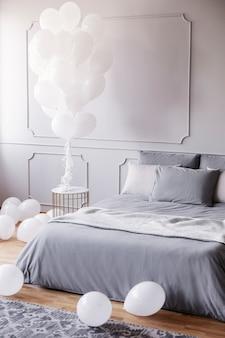 Witte ballonnen in stijlvolle grijze slaapkamer met comfortabel kingsize bed met grijs beddengoed en deken, echte foto met kopieerruimte op de lege muur
