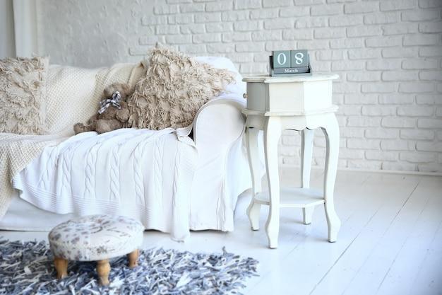 Witte bank en nachtkastje met omschakelkalender in een stijlvolle woonkamer. foto met kopie ruimte