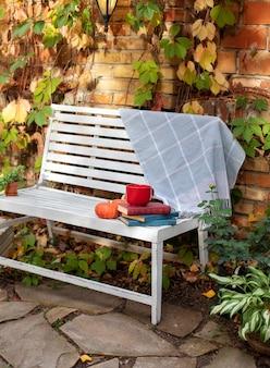 Witte bank in de herfsttuin. in de achtertuin groeien decoratieve groene planten en chrysanten. stapel boeken, kopje thee, plaid en pompoen liggen op een houten bankje