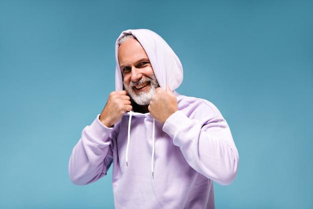 Witte bebaarde man in hoodie glimlachend op blauwe muur