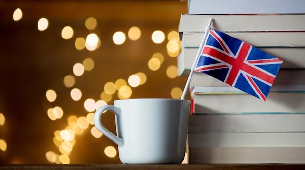 Witte beker en groot-brittannië vlag in de buurt van stapel boeken