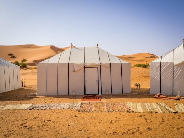 Witte berbertenten in de sahara, marokko met tapijten op de zanderige grond