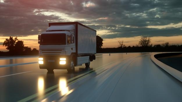Witte bestelwagen op asfaltweg bij zonsondergang