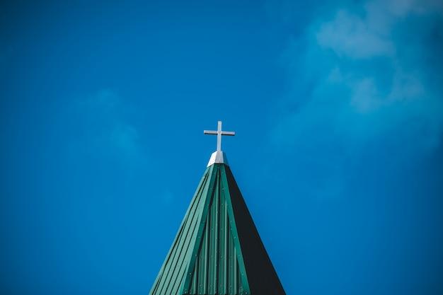 Witte betonnen kruis onder heldere blauwe hemel Gratis Foto