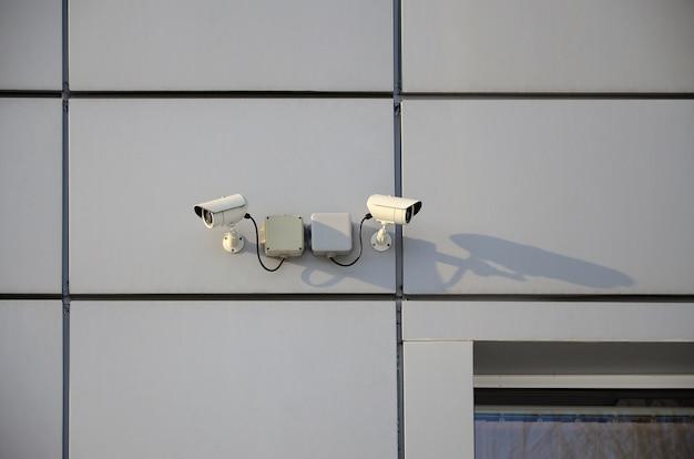 Witte bewakingscamera ingebouwd in de metalen wand van het kantoorgebouw