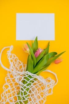 Witte blanco met lente boeket van veelkleurige tulpen in eco tas op een gele achtergrond