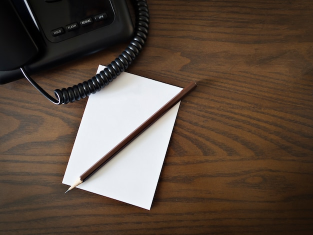 Witte blanco papier, potlood en telefoon op bruin houten tafel