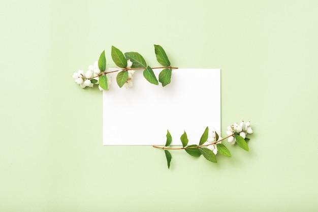 Witte blanco papieren kaart of notitie met maretak bloem, bovenaanzicht