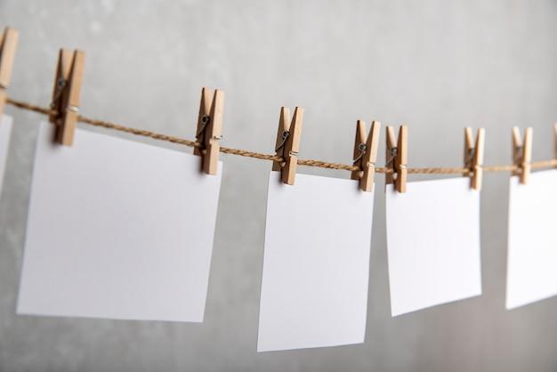 Witte blanco papieren notities hangen met wasknijpers aan touw. grijze achtergrond. ruimte kopiëren.