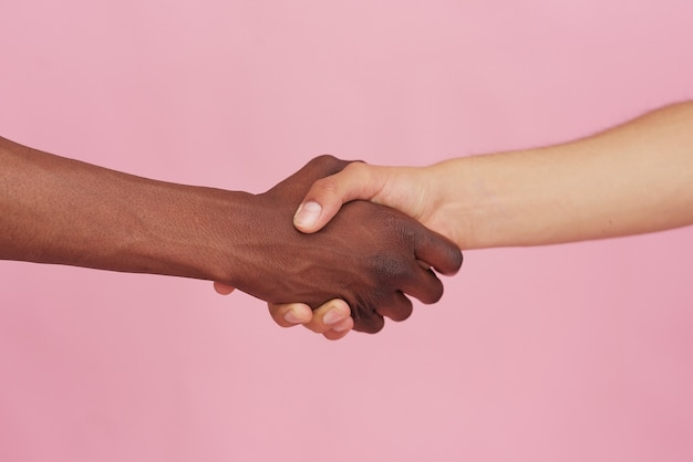 Witte blanke hand en zwarte hand schudden handen op roze achtergrond. multiraciaal respect en begrip concept.