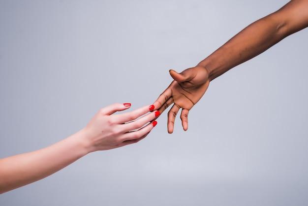 Witte blanke vrouwelijke hand en zwarte mannelijke hand die vingers bij elkaar houden