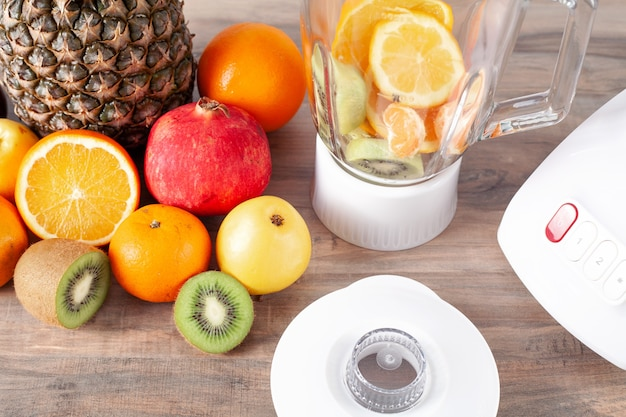 Witte blender met vers fruit op tafel.