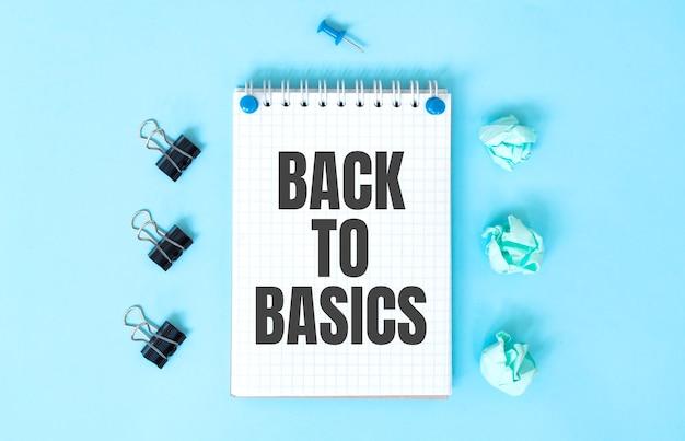 Witte blocnote met tekst back to basics en office-tools op de blauwe achtergrond