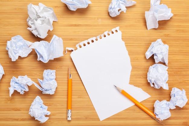 Witte blocnote op een houten tafel. rond de notitieblokken ligt veel verfrommeld papier