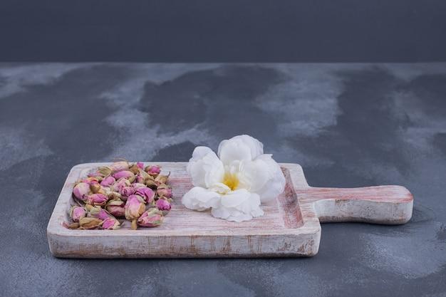 Witte bloem en bloemzaden op blauwe oppervlakte.