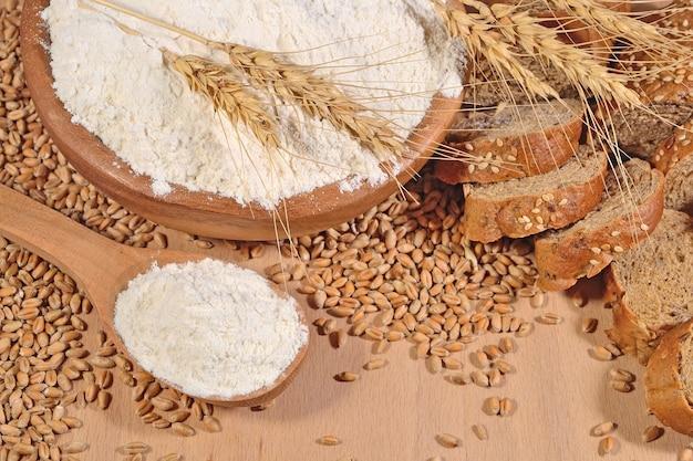Witte bloem in een houten lepel, tarwe en brood op een houten ondergrond