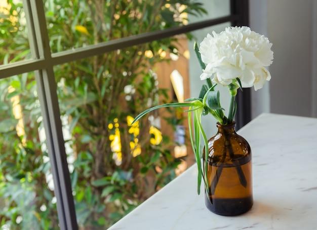 Witte bloem in grasfles op witte lijst met glasvenster