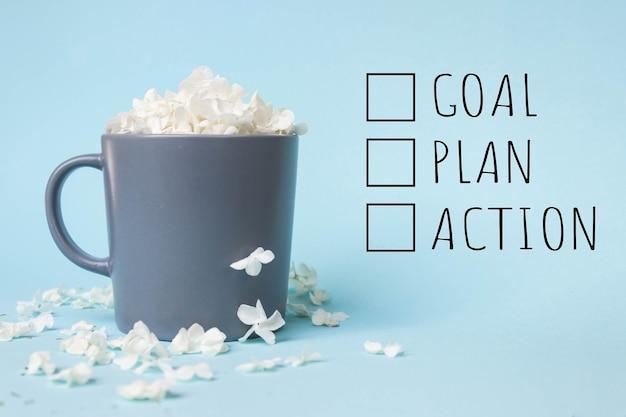 Witte bloemblaadjes in een grijze kop op een blauwe achtergrond met het opschrift doel, plan, actie