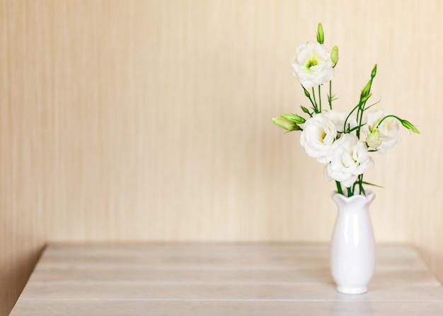 Witte bloemen eustoma of lisianthus in vaas op houten tafel met kopie ruimte.