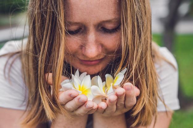 Witte bloemen frangipani plumeria in vrouwelijke handen