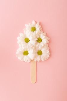 Witte bloemen gerangschikt op een ijsstokje op een roze achtergrond. lente concept minimaal plat leggen,