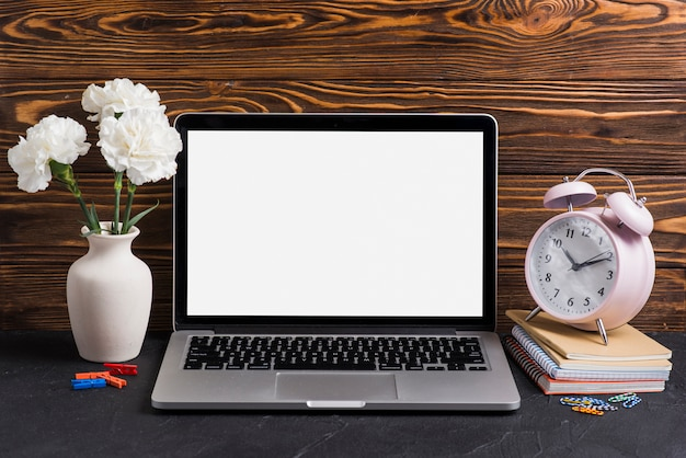 Witte bloemen in de vaas; laptop en wekker op notebooks tegen houten achtergrond
