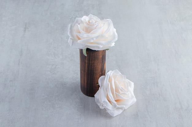 Witte bloemen in een houten kruik, op de witte tafel.