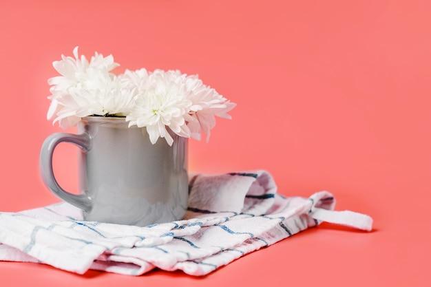 Witte bloemen in een theekop. bloemensamenstelling op een pastel achtergrond