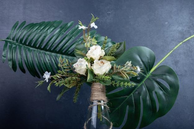 Witte bloemen in keramische vaas op donkere muur.