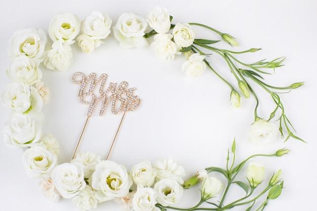 Witte bloemen met een kader en de inscriptie mr. en mrs.