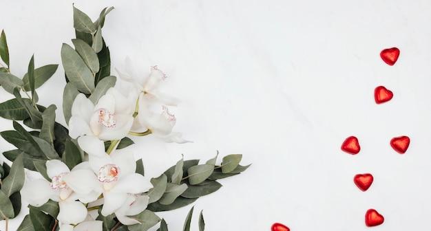 Witte bloemen met eucalyptus en rode chocolaatjes