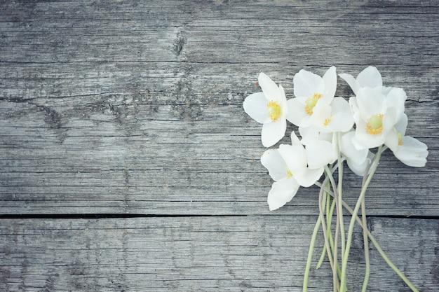 Witte bloemen op oude houten achtergrond. tuinbloemen op houten lijstachtergrond.