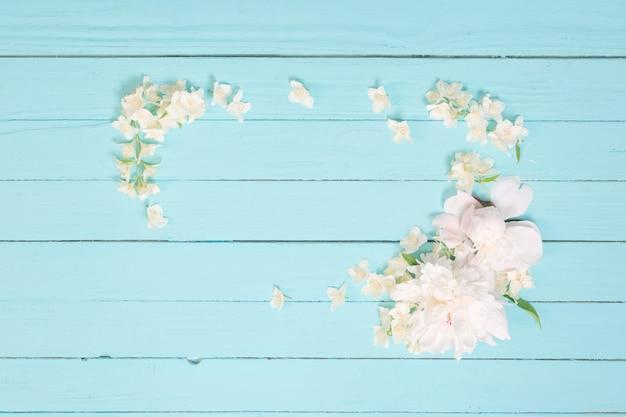Witte bloemen op witte houten muur