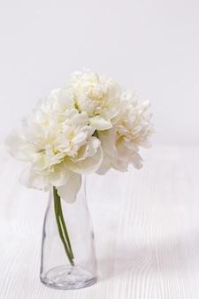 Witte bloemen pioenrozen in glazen vaas. stilleven. concept van houten moeder, valentijnsdag.