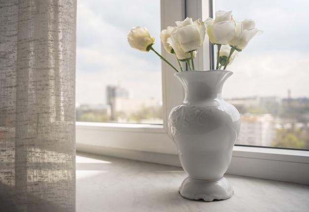 Witte bloemenvaas naast het raam