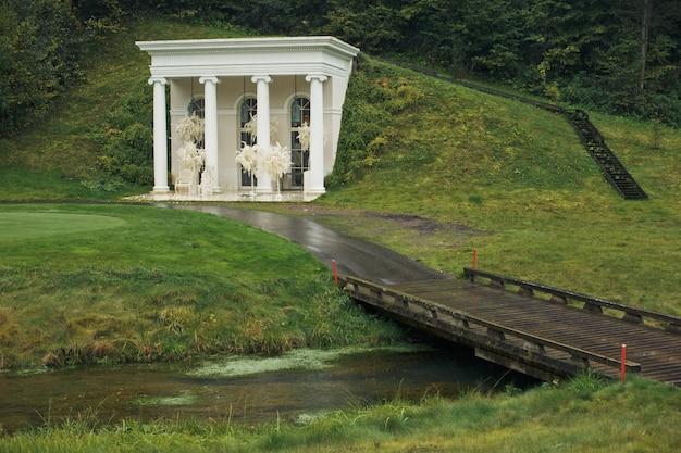 Witte boeketten hangen van de pijlers van het witte huis op de groene heuvel