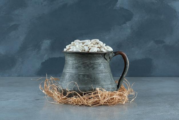 Witte bonen in een metalen etnische pot op droge grassen. hoge kwaliteit foto