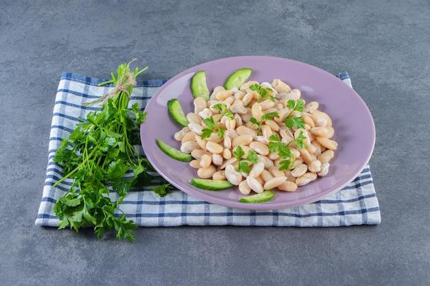 Witte bonen met komkommer op een bord naast peterseliebrunch op een handdoek op het marmeren oppervlak
