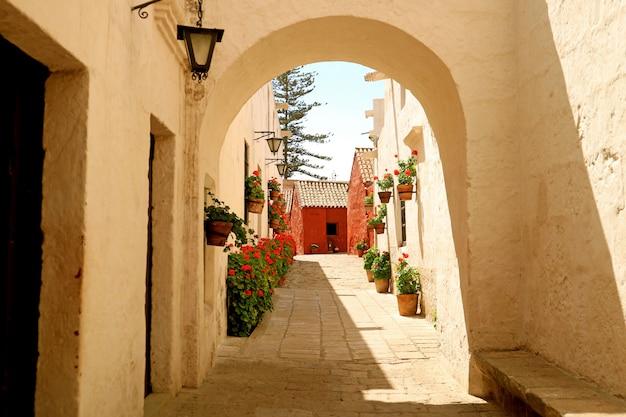 Witte boog die leidt naar de steeg vol met rood bloeiende struiken in het klooster van santa catalina