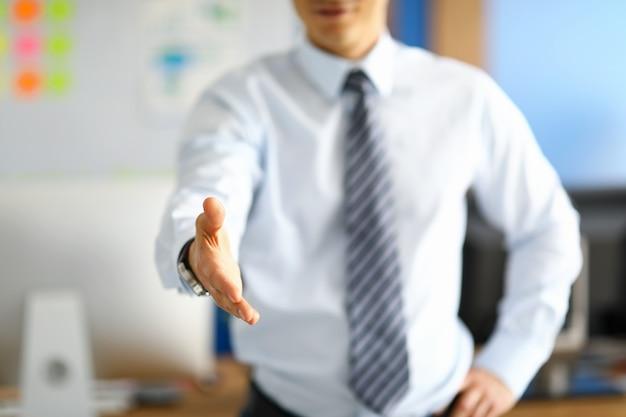 Witte boorden werknemer toont zijn respect door handdruk te bieden