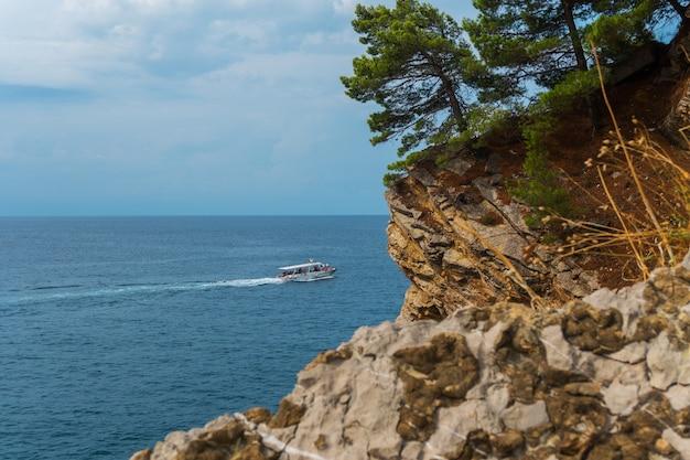 Witte boot en rotsachtige klif met dennen op turquoise zee