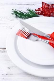 Witte borden, mes, vork, servet en kerstversiering op houten tafel